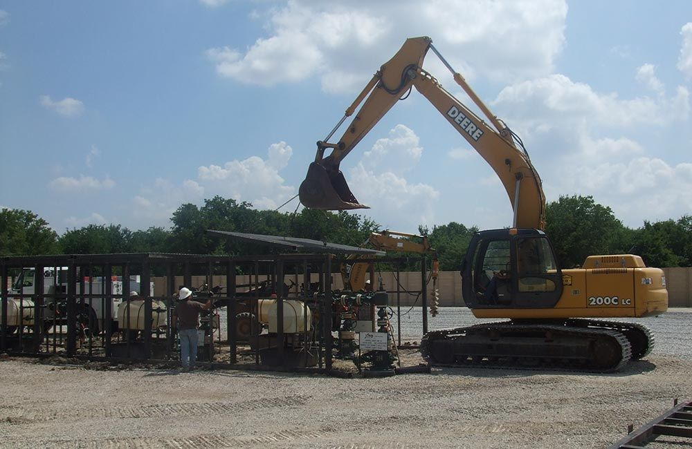 Wellhead enclosure placement with front end loader