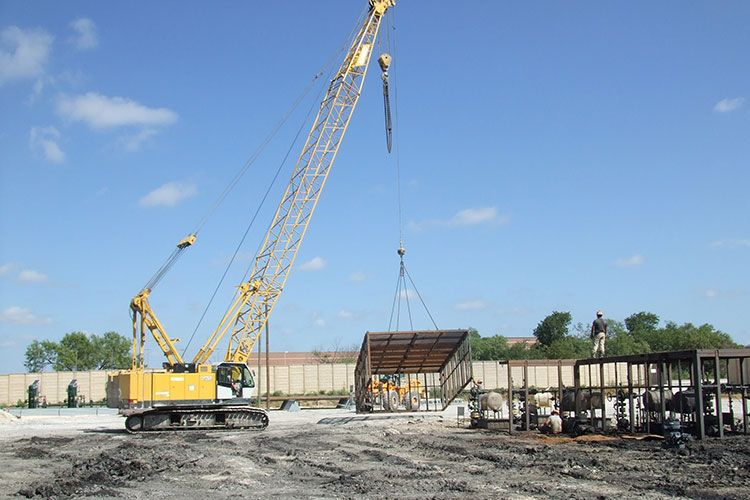 Protective wellhead enclosure being placed by crane